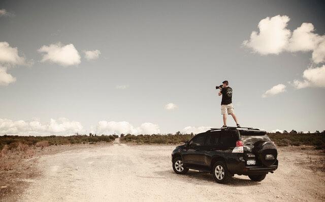 Shaun Atherstoneon top of a car taking photos